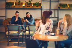 Girls are sitting at a table and waving guys at another table Stock Photos