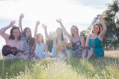 Girls Sitting Together in Grassy Field Singing and Playing Music Stock Image
