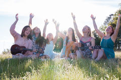 Girls Sitting Together in Grassy Field Singing and Playing Music Royalty Free Stock Photo