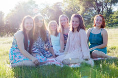 Girls Sitting Together in Grassy Field With Sunlight Overhead. Group of Girls Sitting Together in Grassy Field With Sunlight Overhead stock image