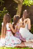 Girls sitting under tree at park and braiding each other Royalty Free Stock Photography