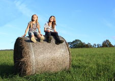 Girls sitting up on package of hay Stock Photos