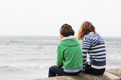 Girls sitting on wall looking at sea Stock Photo