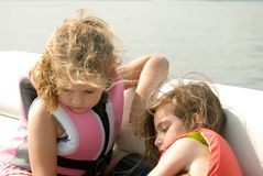 Girls Sitting By Water Playing royalty free stock photos