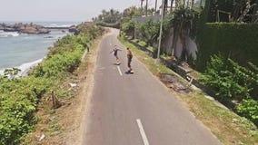Girls Skating Ocean aerial slow motion. Aerial of two girls skateing next to the ocean. 50FPS shot stock video