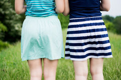 Girls in skirts. Girls in short cotton skirts shot from behind, summer feeling royalty free stock images