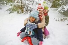 Girls on sledge. Little girls sitting on sledge in winter park Stock Image