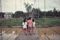 Girls on the sling bridge over Yom River Royalty Free Stock Photography