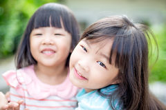 Girls smile happily in park Stock Photo