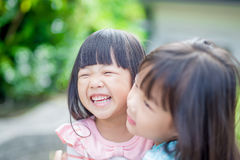 Girls smile happily in park Stock Images