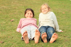 Girls with smileys on toes. Barefoot kids - funny girls with twenty smileys on toes of their bare feet Stock Images