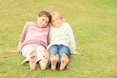 Girls with smileys on toes and soles. Barefoot kids - funny girls with twenty smileys on toes and four on soles of their bare feet Royalty Free Stock Photos