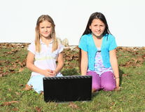 Girls smiling behind a notebook Royalty Free Stock Image