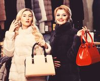Girls with smiling faces in black and white fur coats hold purses in hands. Luxury style concept. Women with blond hair. In fur coats with bags in fur shop royalty free stock photo
