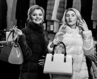 Girls with smiling faces in black and white fur coats hold purses in hands. Luxury style concept. Women with blond hair. In fur coats with bags in fur shop stock photos