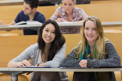 Girls smiling in lecture hall with tablet pc. In college Royalty Free Stock Images