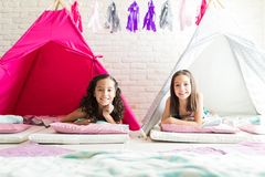 Girls Smiling While Resting In Tipi Tents During Sleepover. Cute girls smiling while resting in tipi tents during sleepover at home stock photography