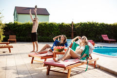 Girls smiling, sunbathing, lying on chaises near swimming pool. royalty free stock photos