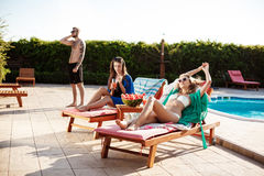 Girls smiling, sunbathing, lying on chaises near swimming pool. royalty free stock photography