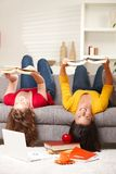 Girls smiling upside down on sofa stock photos