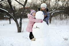 Girls with snowman Royalty Free Stock Image