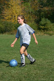 Girls Soccer. A young girl has fun kicking a soccer ball Royalty Free Stock Images