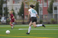 Girls soccer player after the ball Stock Photography