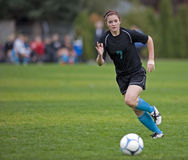 Girls soccer player running with ball