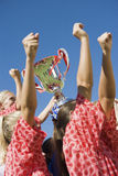Girls Soccer Team With Trophy Against Blue Sky. Low angle side view of happy girls soccer team with trophy against clear blue sky Royalty Free Stock Photo