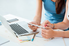 Girls social networking. Teen girls sitting at desk and using a touch screen tablet, they are studying and using apps, hands close up Stock Images