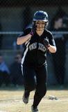 Girls softball - batter runs to first Royalty Free Stock Photography