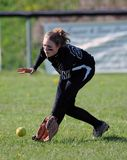 Girls softball - fielding in the outfield. RACHEL, WV - APRIL 21: A North Marion HS (WV) softball player fields a grounder in the outfield prior to a game Royalty Free Stock Image