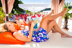 Girls in sound loungers at beach bar Stock Photos