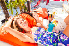 Girls in sound loungers at beach bar Royalty Free Stock Photos