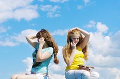 Girls speaking by mobile against blue sky Royalty Free Stock Photography