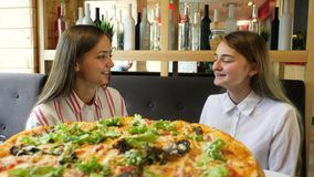 Girls spend time in a pizzeria. Two shot. Girls spend time in a pizzeria. Girls talking over lunch. Big pizza stock footage