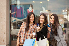 Girls spending money at a shopping mall. Three young Latin girls spending some money at a shopping center and showing their credit cards. Extra copy space Royalty Free Stock Photos