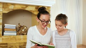 Girls spending time after book reading and sharing impressions, sisters sitting together stock footage