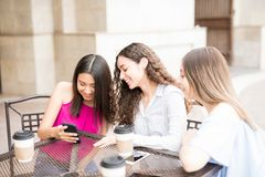 Girls spending time at outdoor cafe. Cute young girl showing a picture on her smartphone to her friends while having some coffee at outdoor cafe stock photography