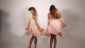 Girls spinning around and volumed skirts rose from wind and from movement of girls. Two beautiful and sweet girls with. Long hair dancing against grey studio stock video footage