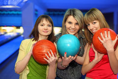Girls stand alongside, hold balls for bowling. Girls closely stand alongside, hold balls for bowling and smile royalty free stock images