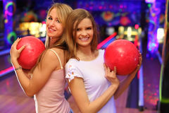 Girls stand and keep ball in bowling club Stock Photography