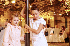 Girls stand near decorative lamp post Stock Images