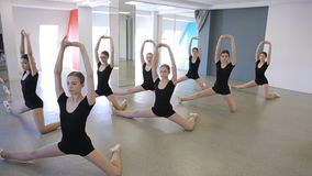 Girls stand in pose and do stretching exercise in dancing class stock video