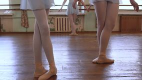 Girls stand in third position and begin to dance in ballet classroom. Girls stand in third position and begin to dance during ballet lesson in ballet classroom stock video