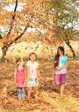 Girls standing barefoot under falling leaves Royalty Free Stock Photography