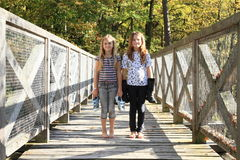 Girls standing on bridge with boots on hands Stock Images
