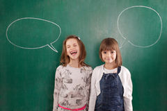 Girls standing in front of chalkboards with speach bubbles Stock Photos