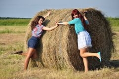 Girls standing by haystacks Stock Images