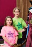 Girls standing near costumes in youth theater. Two girls standing near costumes for a youth theater program Stock Image